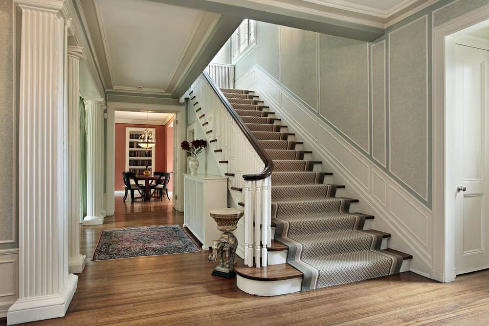 The charming foyer offers a straight staircase with wood treads wrapped in diamond patterned runner and framed with white wooden balustrade against a full wainscoted wall.