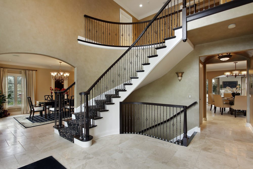 A curved staircase with black railings and stylish carpet floors.
