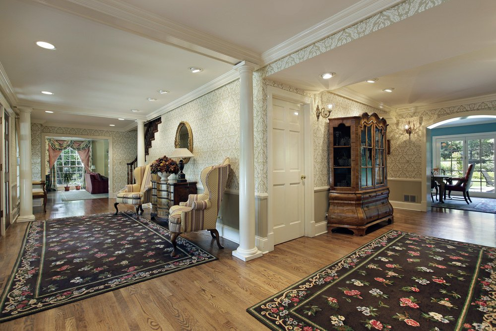 This elegant foyer features beautiful rugs and stylish walls, along with a couple of classy chairs. This foyer is lighted by recessed ceiling lights and wall lighting.