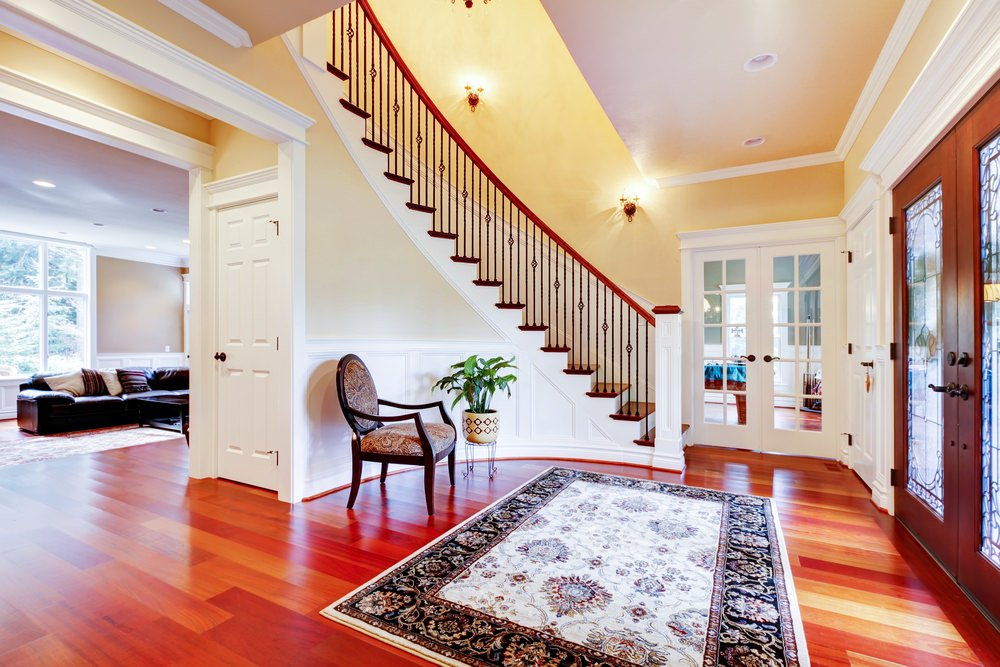 Large foyer boasting a rustic flooring topped by an elegant rug. The staircase lighted by wall lighting look classy while the chairs and an indoor plant on the side add style to the foyer.