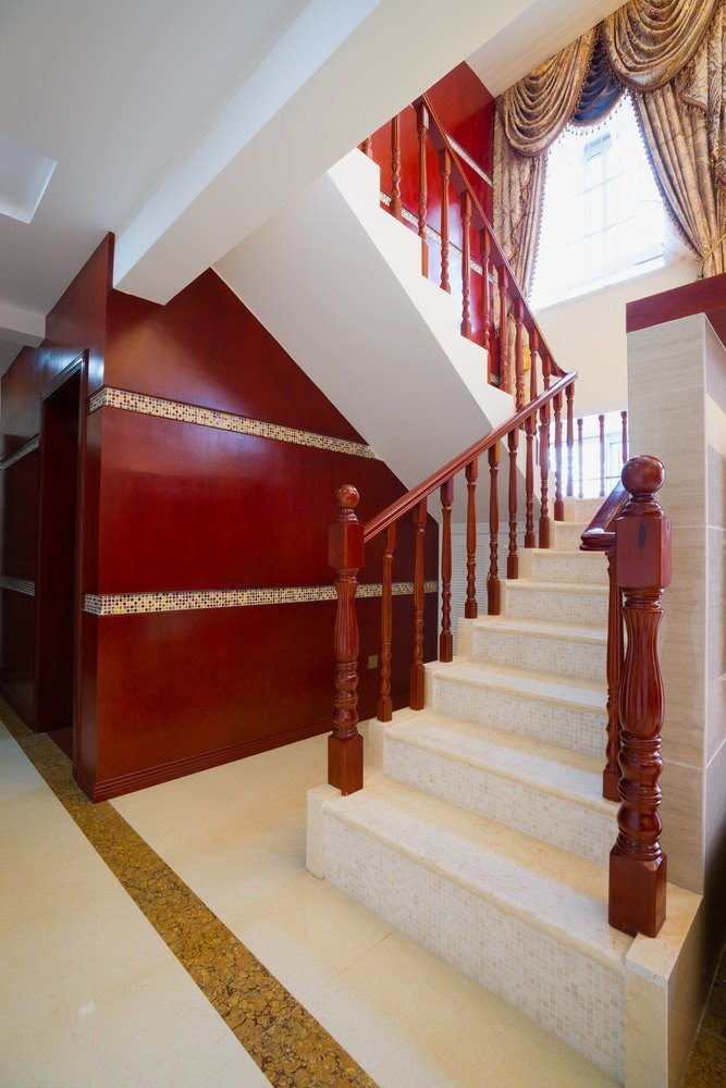 Using red colors punctuate this classically styled staircase. It also has tiles floors and a glamorous pair of window curtains.