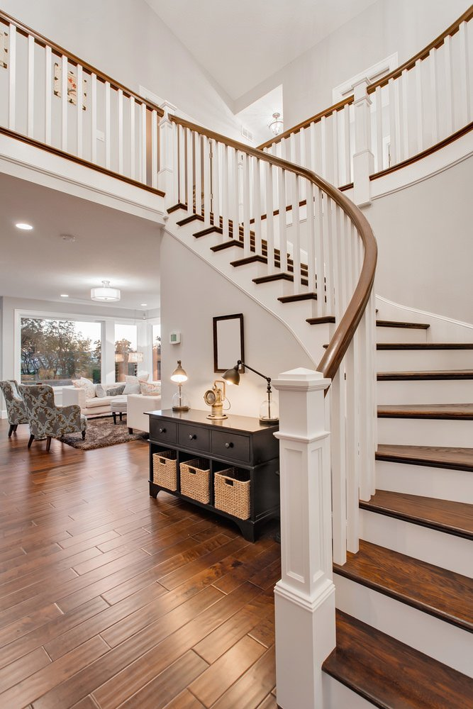 The transitional foyer features a black console table topped with desk lamps and paired with a mirror mounted on the white stairway beautifully contrasted with wood treads and handrail.