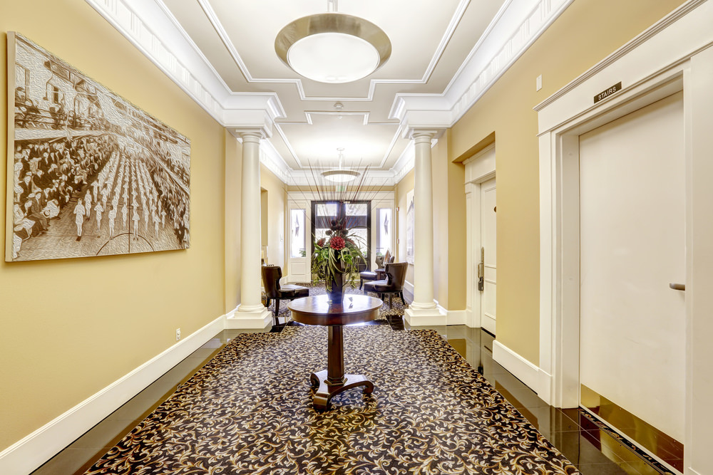 This elegant foyer boasts a very stylish rug set on a sparkling tiles flooring. The ceiling is stunning, perfectly matched by pendant lights. The wall decor looks stylish while the seats on both sides add style to the foyer.