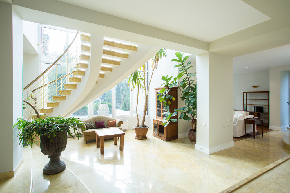 This  beautiful foyer features a classy staircase. Underneath is a small couch and a center table. On the side is the indoor plants adding color to the house.