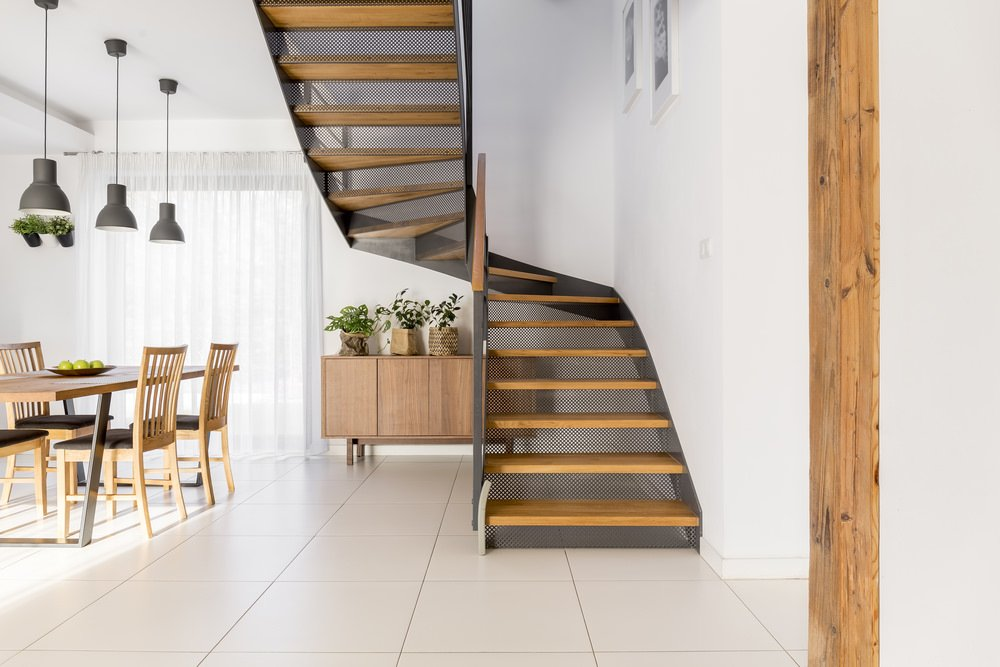 A fresh dining area with white tile flooring which features a staircase that has perforated steel risers and wood tread.