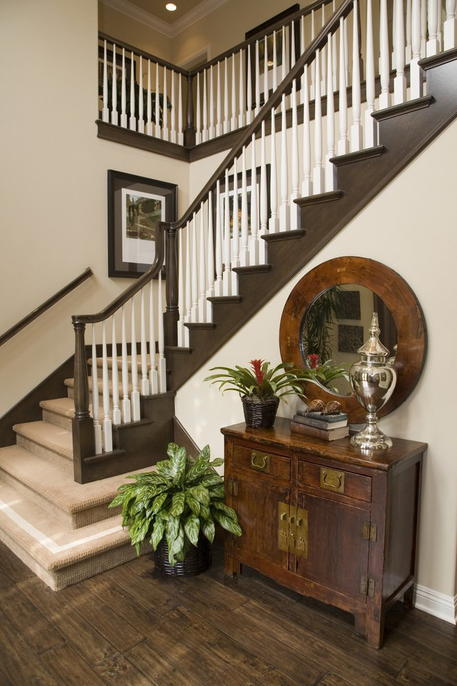 This staircase's floors are covered by carpet. The railings are painted with white and brown while the walls are designed with wall decors.