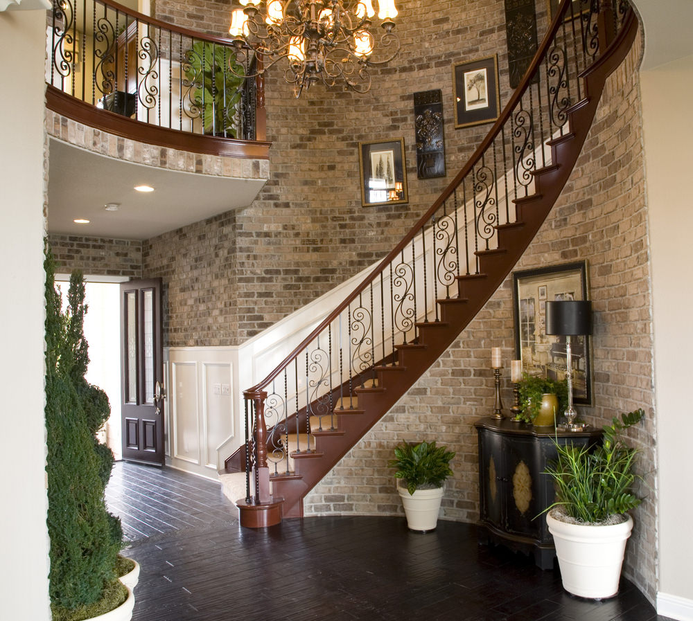 Warm entryway filled with potted plants that create a refreshing ambiance. There's a wooden staircase covered in beige carpet and fitted with an ornate steel balustrade fixed to the stone brick wall with white wainscoting.
