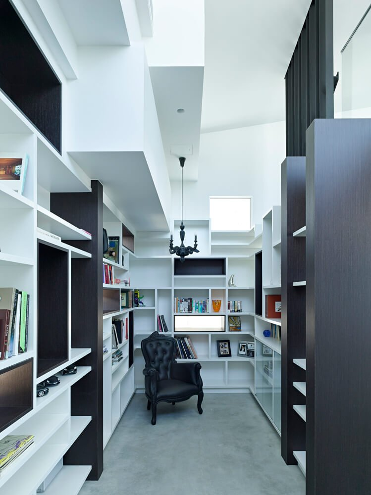 Small and modern home library with multiple shelves surrounding the area.