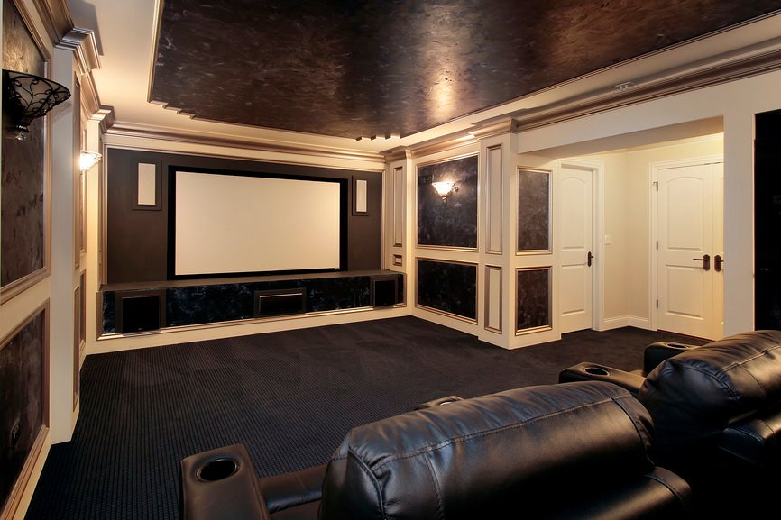 This stylish home theater boasts elegant black and white shade surrounding the room. The carpet flooring and elegant black leather seats look very classy.