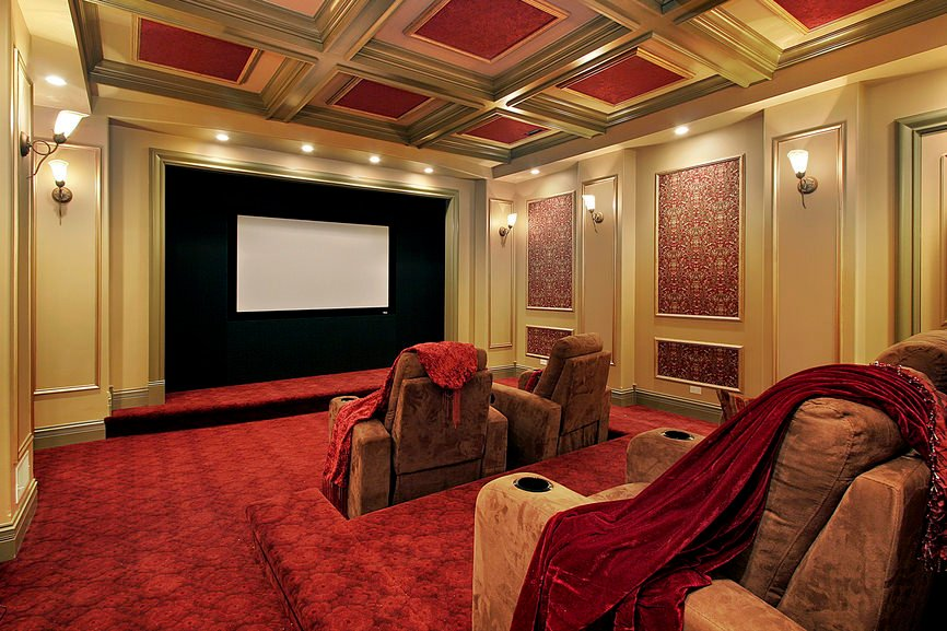 This home theater boasts an elegant red and gold ceiling matching both walls and flooring. The wall lights and recessed lighting look very classy.