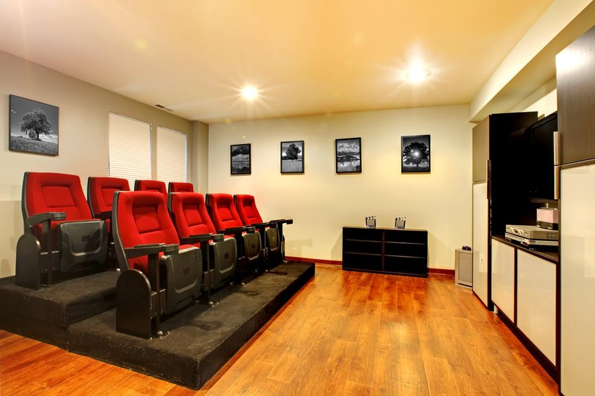 This home theater features white ceiling and walls along with hardwood flooring. The theater seatings look so lovely.