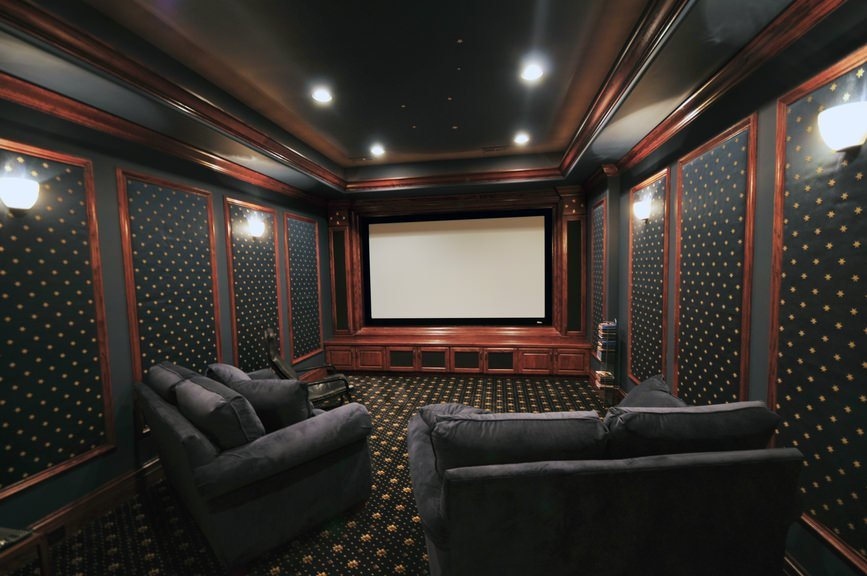 This home theater features very elegant walls and floors matching the stunning tray ceiling. The wall lights and recessed lighting look perfect for the room.