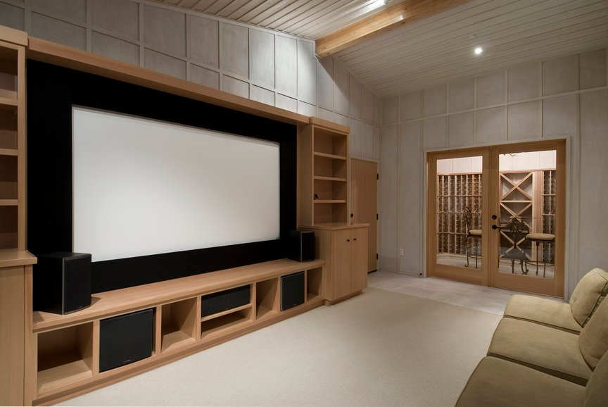 Simple yet classy home theater with white walls and floors topped by a large rug.