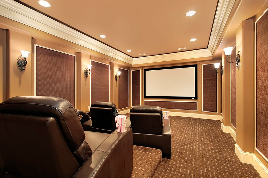 Large home theater featuring brown carpet flooring matching the brown shade on the walls lighted by wall lighting.
