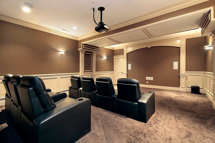 Large home theater with brown and white walls and ceiling, along with a lovely carpet flooring and elegant black theater seats.