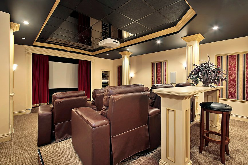 A large home theater room with an elegant black and gold ceiling lighted by lovely recessed lights.