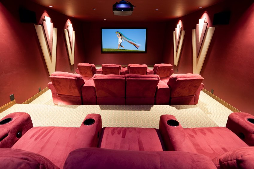 The red theater seats matching the red walls with stylish decors add elegance to this home theater set up.