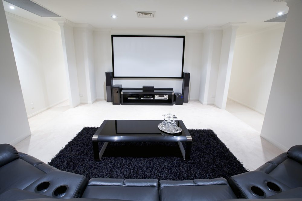 White home theater equipped with black furniture set and rug.