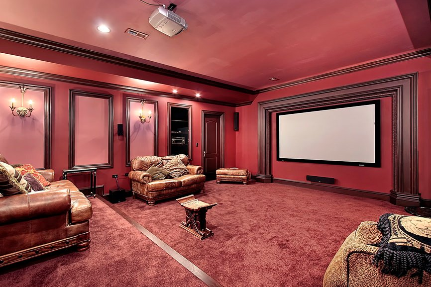 Large home theater featuring red walls, ceiling and carpet flooring. The seats look very elegant and comfortable.