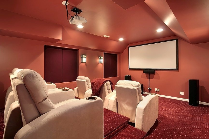 This home theater boasts stylish ceiling and red classy carpet flooring.