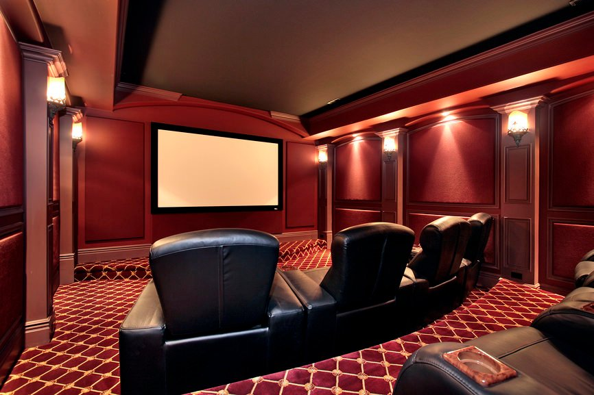 The red finish of the walls and the red and gold combination of the carpet flooring make this home theater look so elegant.
