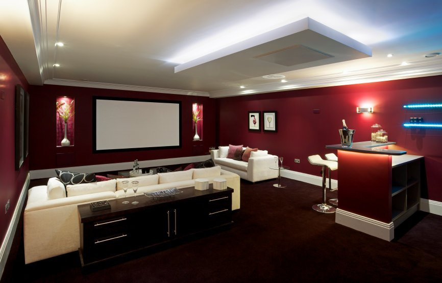 This modern media room boasts a theater space with sectional sofa seats along with a small bar on the side set on the red velvet carpet flooring matching the red elegant walls.
