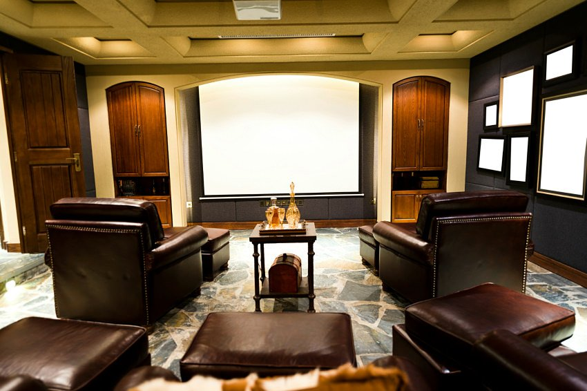 A very classy home theater with elegant theater seats set on the stylish rug. The black walls with charming decors look very elegant as well.