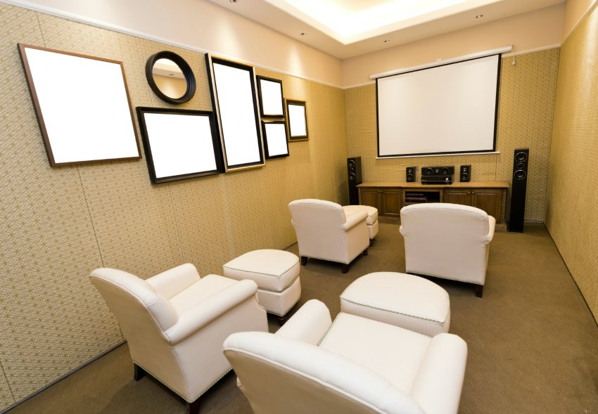 A small home theater featuring white theater seats matching with the white wall decors on the beautiful walls.