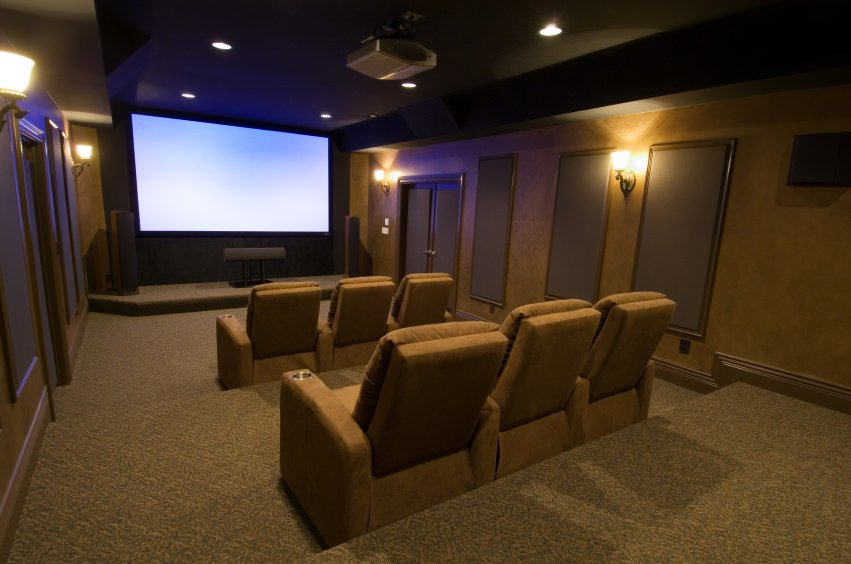 A large home theater with a nice set of theater seats lighted by wall lights and recessed ceiling lighting.