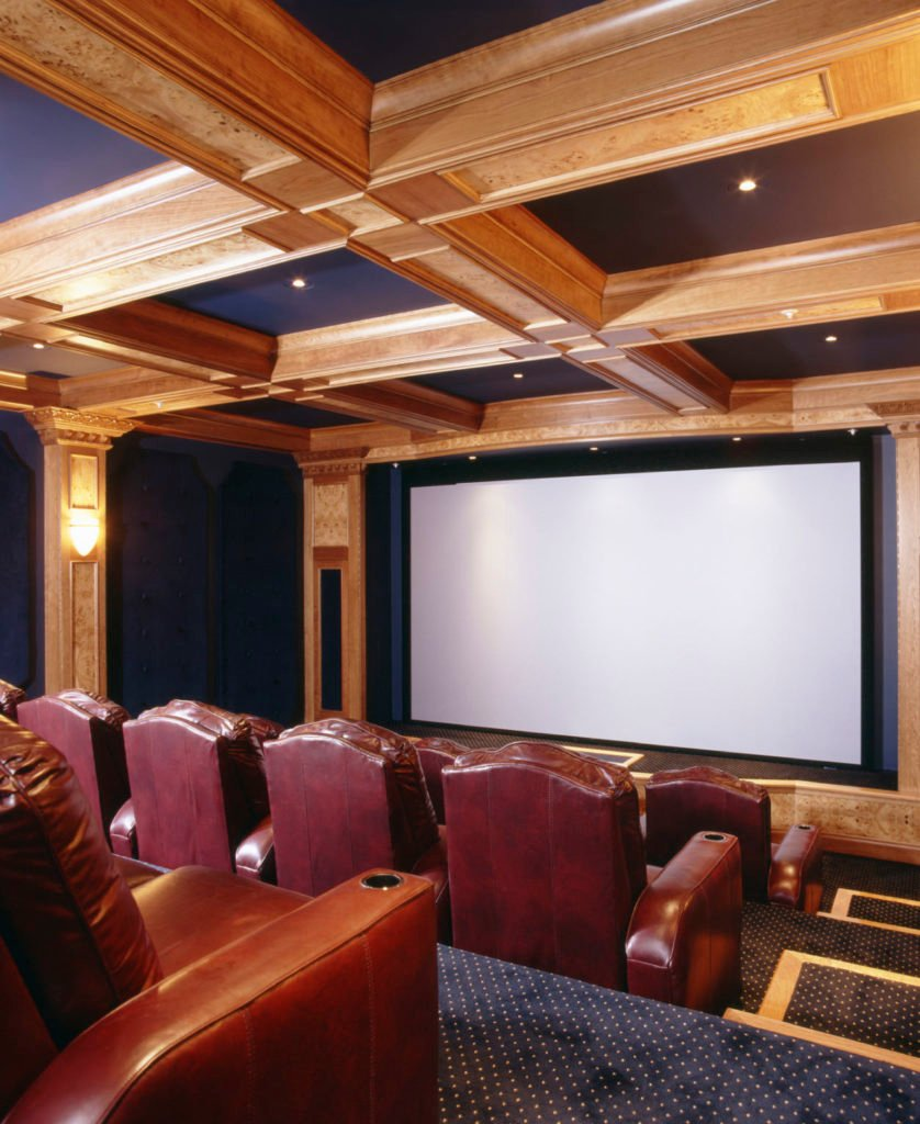 This home theater boasts stylish blue carpet flooring matching the blue shade of the walls and ceiling lighted by wall and recessed lights.