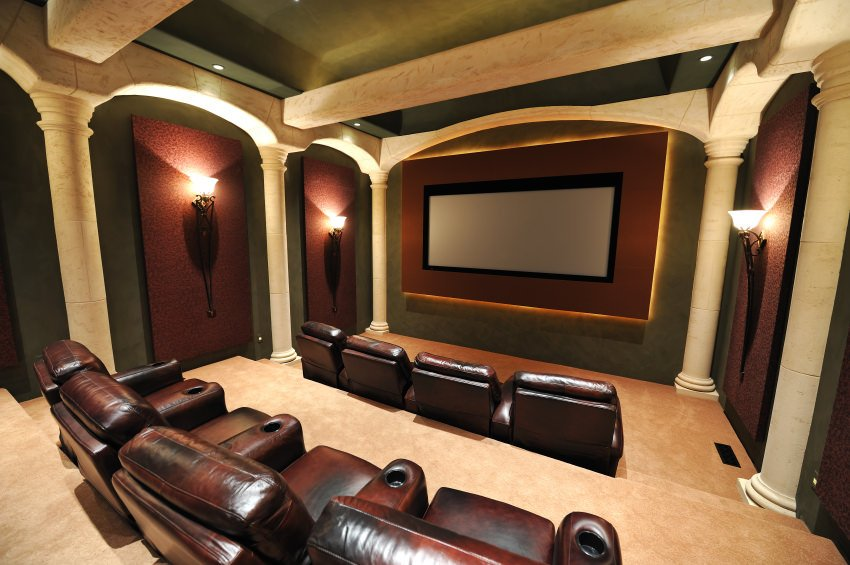 A luxurious home theater featuring elegant walls with lights, along with a stunning ceiling.