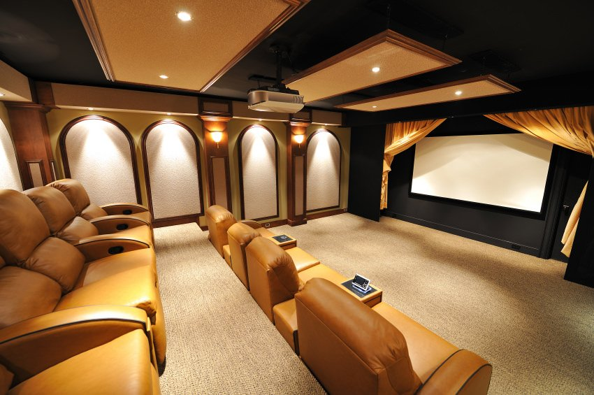 This home theater features a stylish black and gold color combination on both ceiling and walls. The carpet flooring looks perfect together with the theater seats.