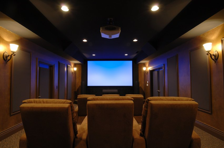 This home theater boasts an elegant black ceiling paired by brown walls and seats. The wall lights and recessed ceiling lighting looks perfect for this room.