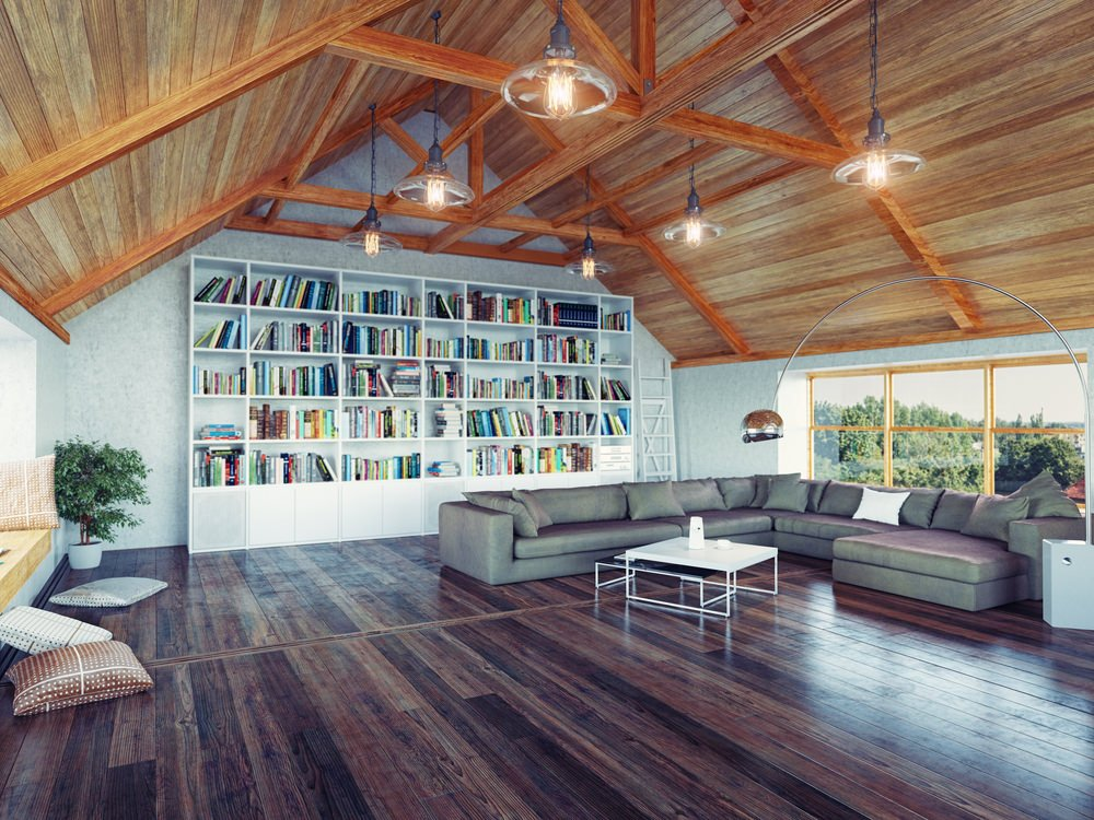 Large living room with a cozy gray sofa set on top of the stylish hardwood flooring. The area features a stunning vaulted ceiling and multiple white bookshelves.