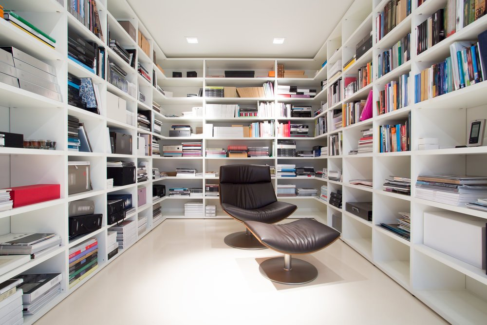 White home library with white shelves and floors. The modern seat is just an eye-catching piece of furniture.