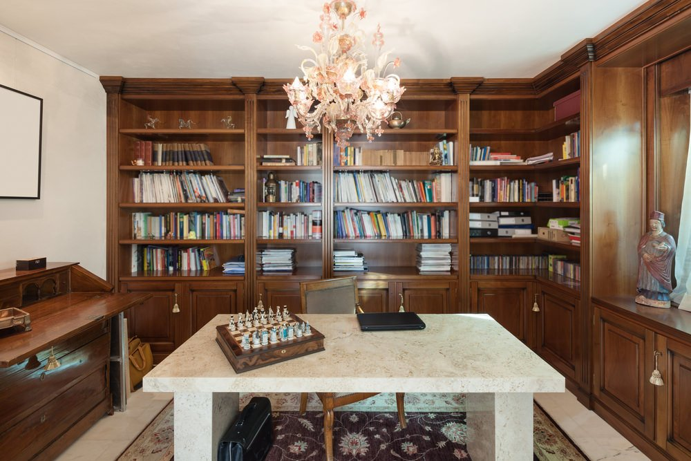 A medium-sized home office with a stunning desk lighted by a glamorous chandelier. The room features multiple bookshelves at the back of the desk and chair.
