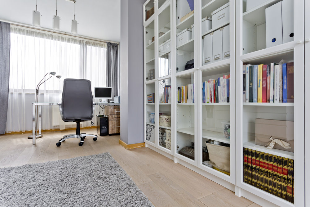 A modish home library with an office desk and chair set on the corner. The white bookshelves are protected by glass doors.