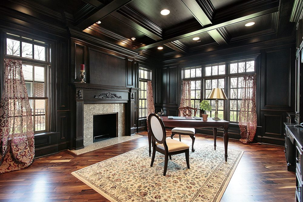 A home office surrounded by handsome black walls and a coffered ceiling. The room also offers a stylish fireplace and a classy rug covering the hardwood flooring.