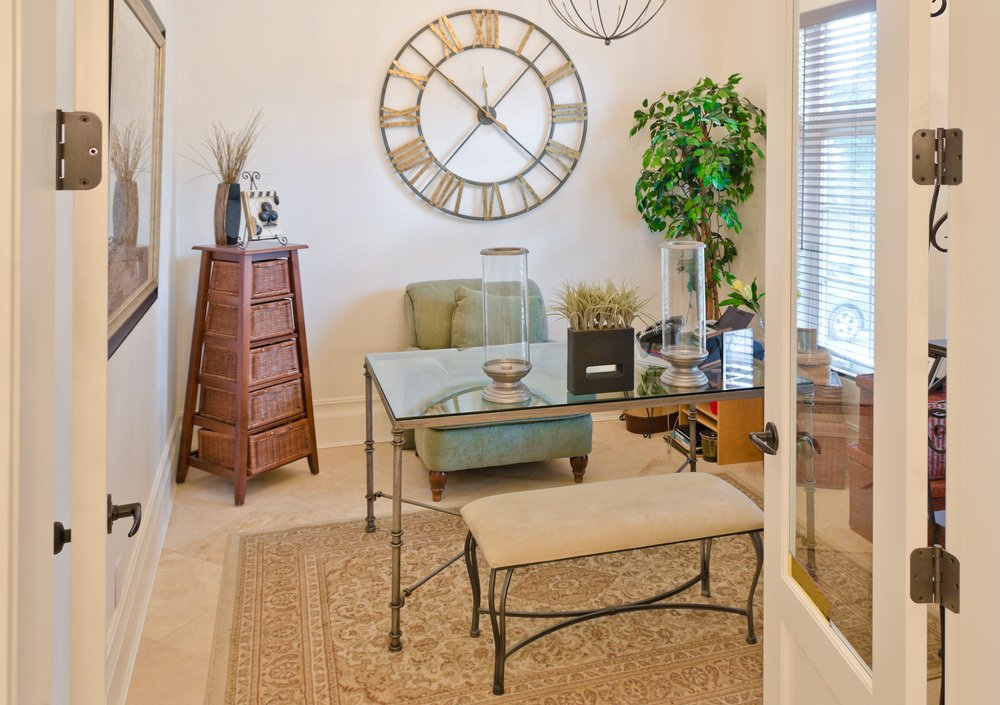 This home office is styled with an oversized wall clock and indoor plant in the corner creating a refreshing ambiance to the room. It includes a glass top desk accompanied by a green comfy chair and beige velvet bench on a vintage rug.