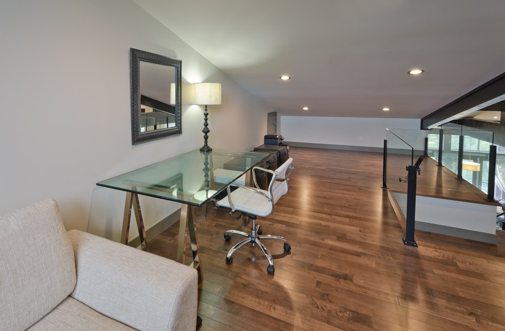 This room offers an office glass desk and a modish chair set on the hardwood flooring. The area has a stylish shed ceiling lighted by recessed lights.