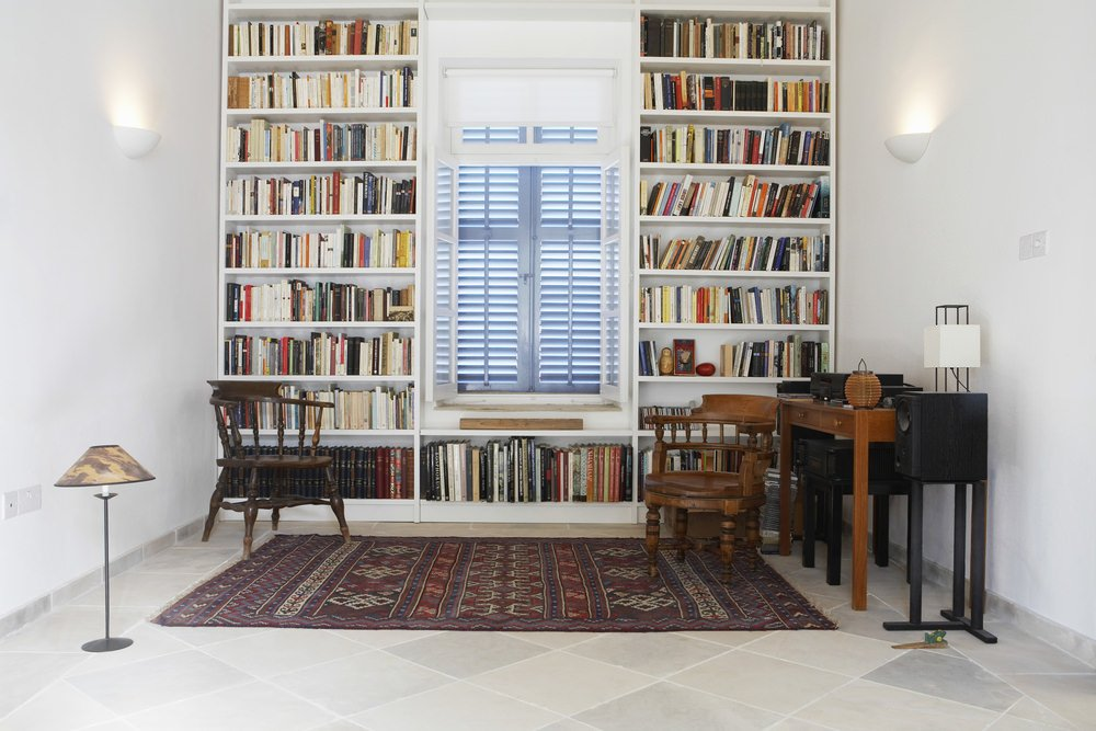 A home office with a library space featuring multiple white bookshelves lighted by wall lights. The tiles flooring is topped by an elegant rug.