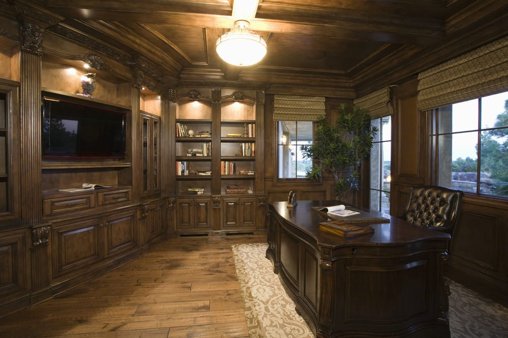 A rustic medium-sized home office with an elegant office desk set on the classy rug set on the hardwood flooring.