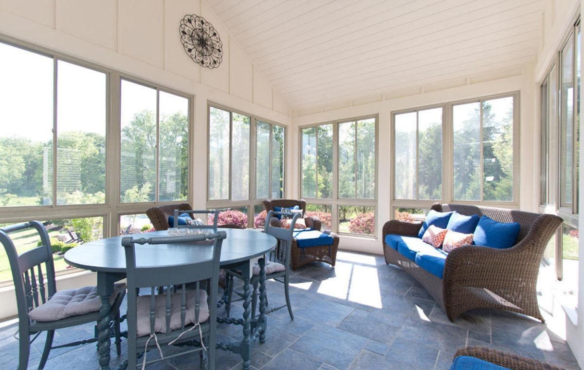 Spacious, farmhouse sunroom with multicolored furnitures and neutral walls.