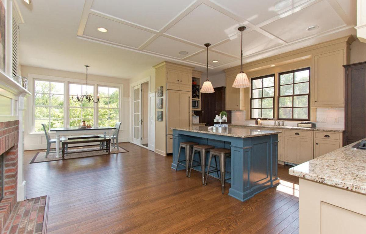 Airy kitchen offers a blue breakfast island lighted by a pair of pendants that hung from the coffered ceiling. It includes a classy dining set by the window that sits on a beige rug.