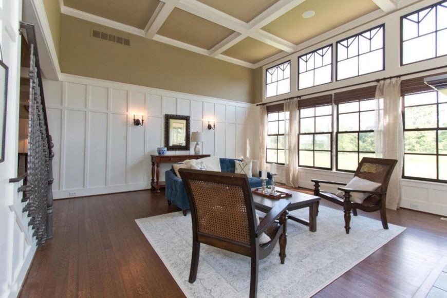 Spacious formal living room featuring hardwood flooring and high coffered ceiling.