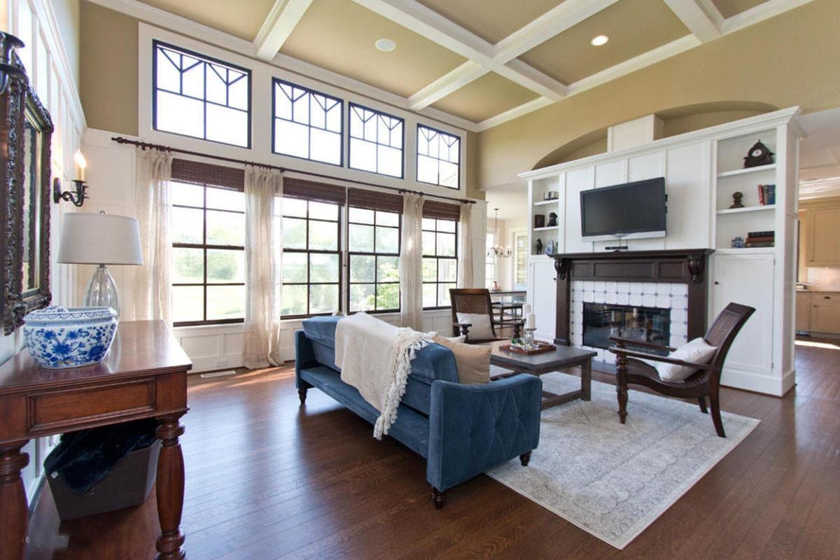 Airy living room with coffered ceiling and wood framed glass windows covered with wicker roman shades and white sheer curtains. It includes a blue sofa paired with wooden coffee table and armchairs.