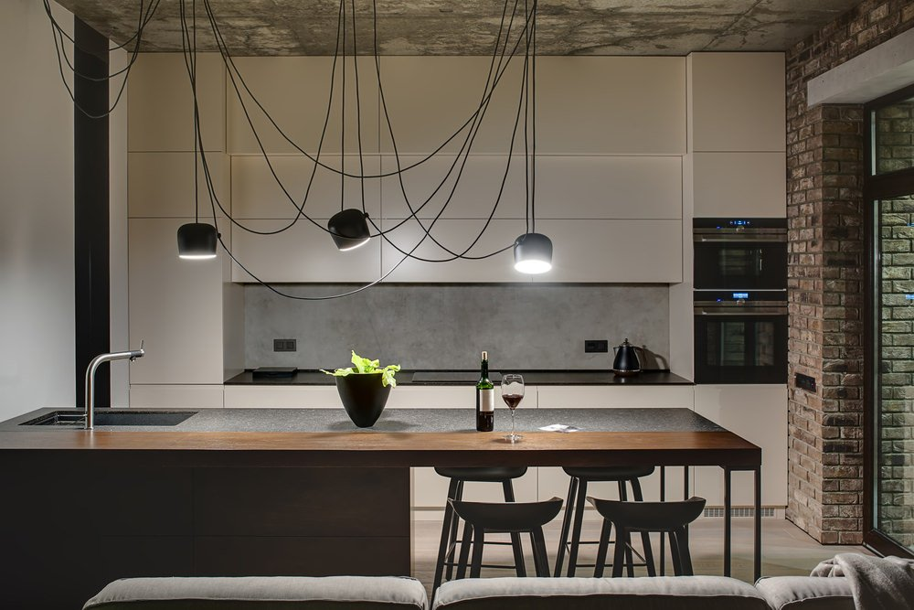 This industrial kitchen boasts an enchanting ceiling lighting just above the center island with a breakfast bar.