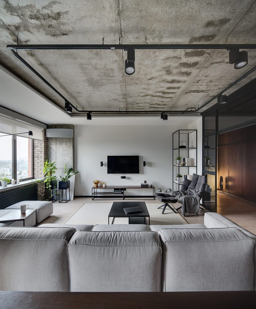 Industrial living room with a faded red brick wall and barrel vaulted ceiling with hanging black pendants. It has a brown velvet sofa and wooden coffee table over a beige rug.