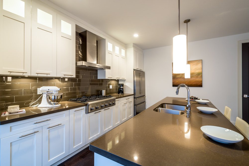 This kitchen features a single wall style with white walls and ceiling lighted by recessed and pendant lights.