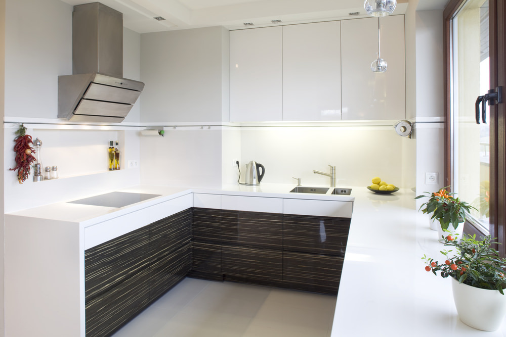 This kitchen features white cabinetry, walls and smooth white countertops.